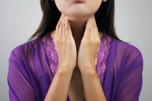 A lady touching her thyroids.