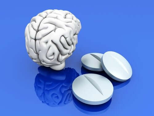 A digital image of a white brain next to three white pills against a blue background.