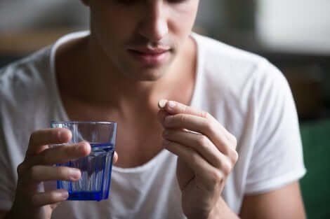 A person holding a pill and a glass of water.