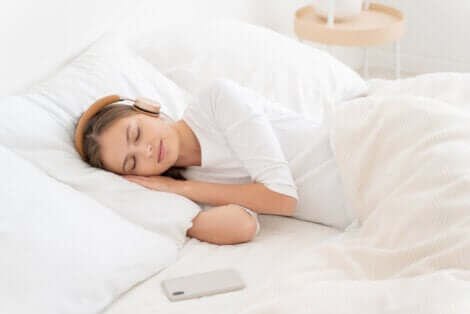 A woman listening to headphones while sleeping.