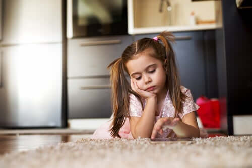 A child lying on the floor looking thoughtful.