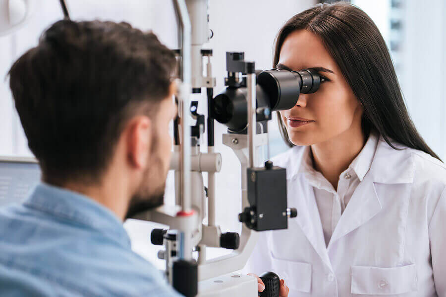 An optometrist examining a woman's eyes.