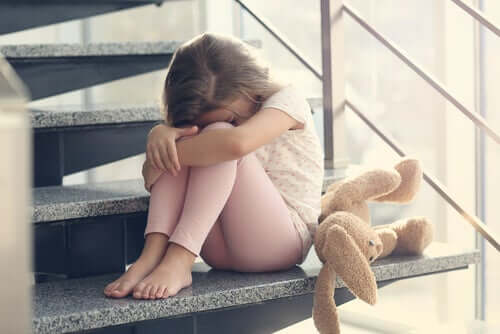 A child crying on the stairs next to a stuffed bunny.