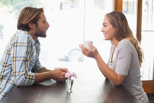 A couple having a dialogue at a table while drinking coffee.