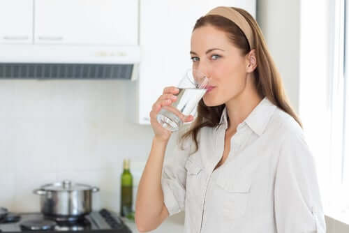A woman smiling and drinking a glass of water while standing in her kitchen.