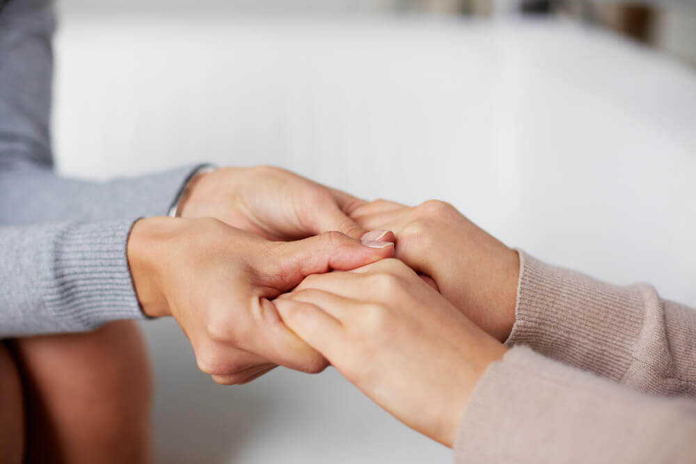 Two people facing one another and holding hands as they speak.