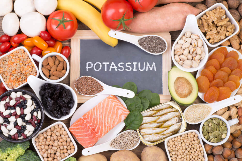 """A variety of potassium sources surrounding a small chalkboard with the word """"potassium"""" written on it."""
