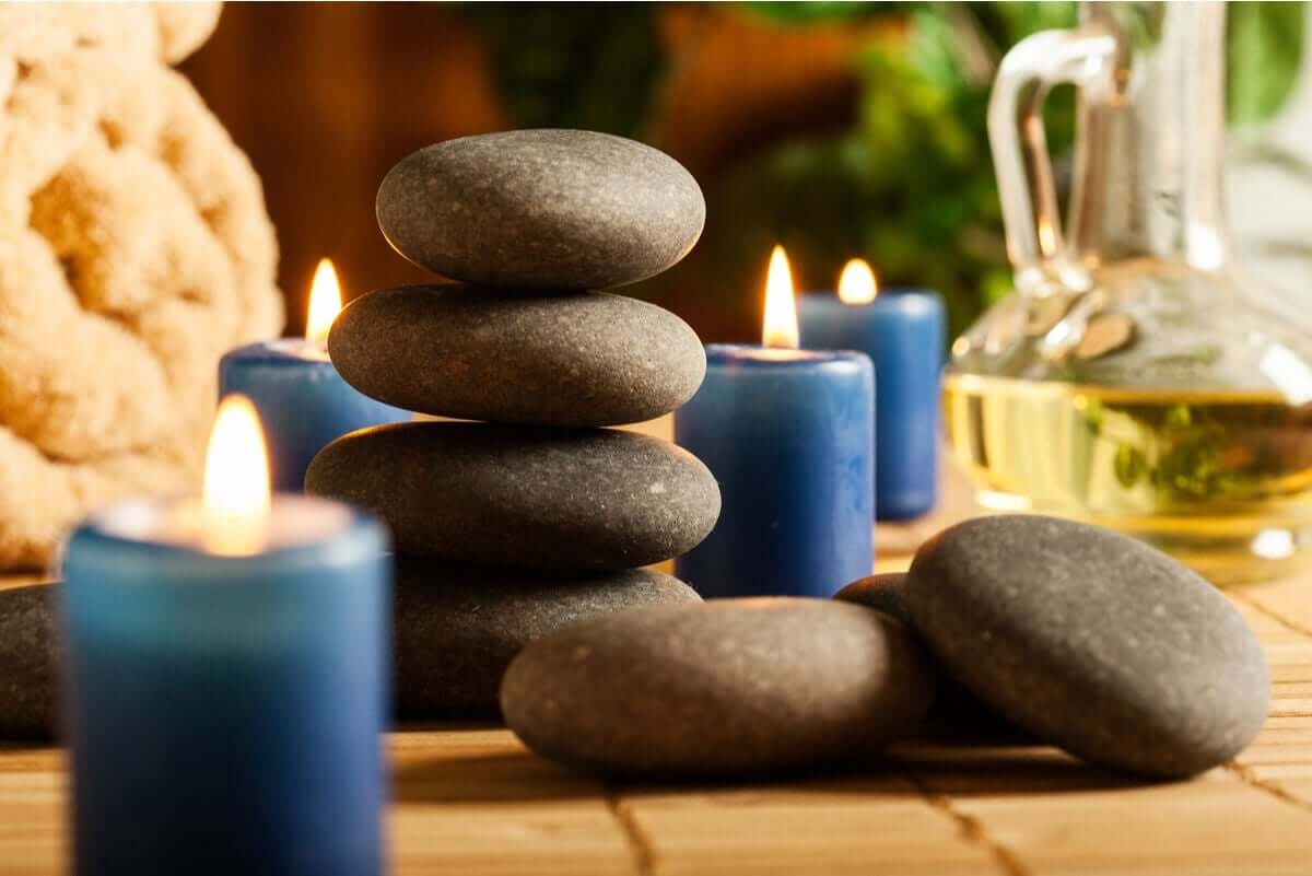 A pile of hot stones surrounded by small blue candles, spa towels, and a bottle of oil.