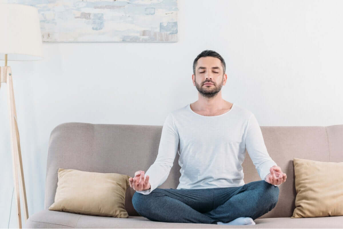 A man sitting cross-legged and meditating on a couch.