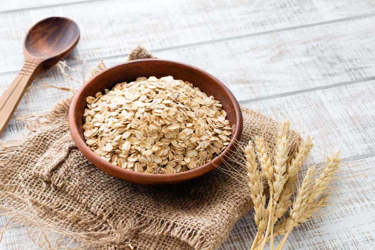 A wooden cereal bowl of dry oats.