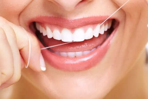 A woman smiling while she flosses her teeth.