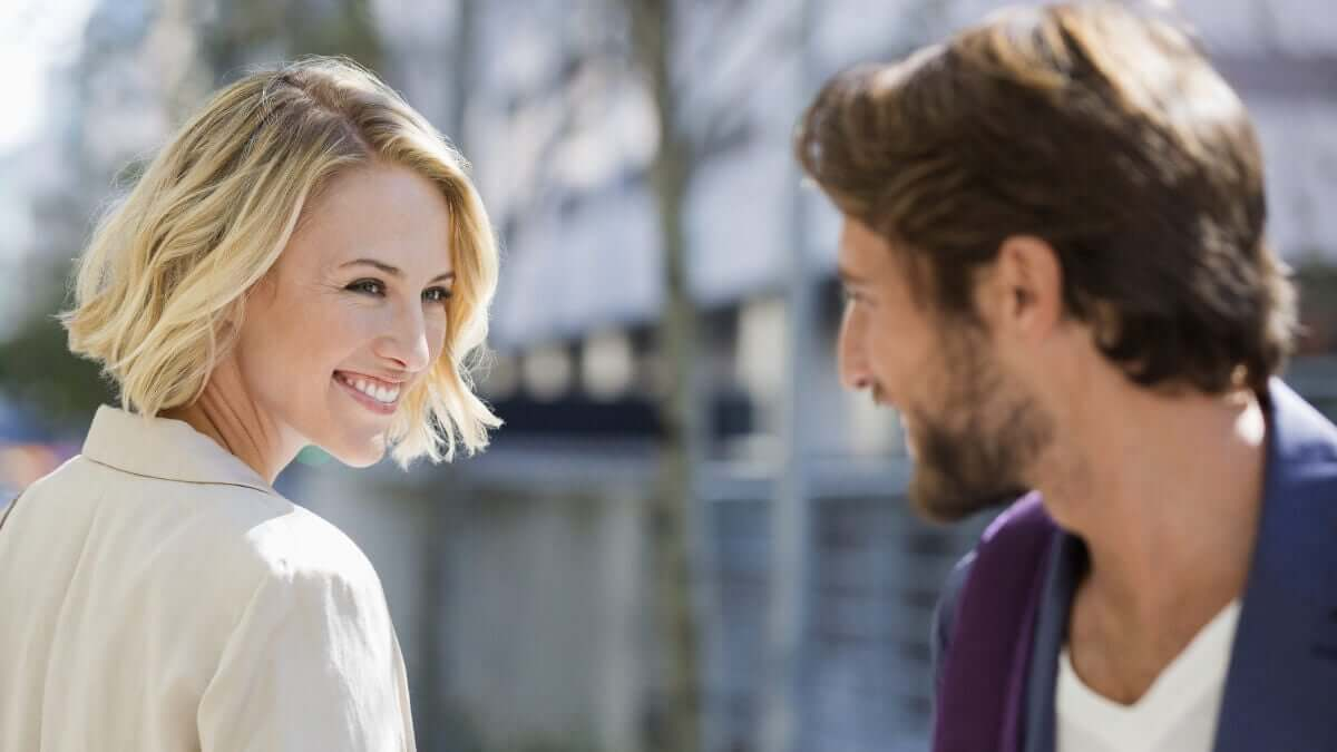 A man and a woman smiling at one another on the street.