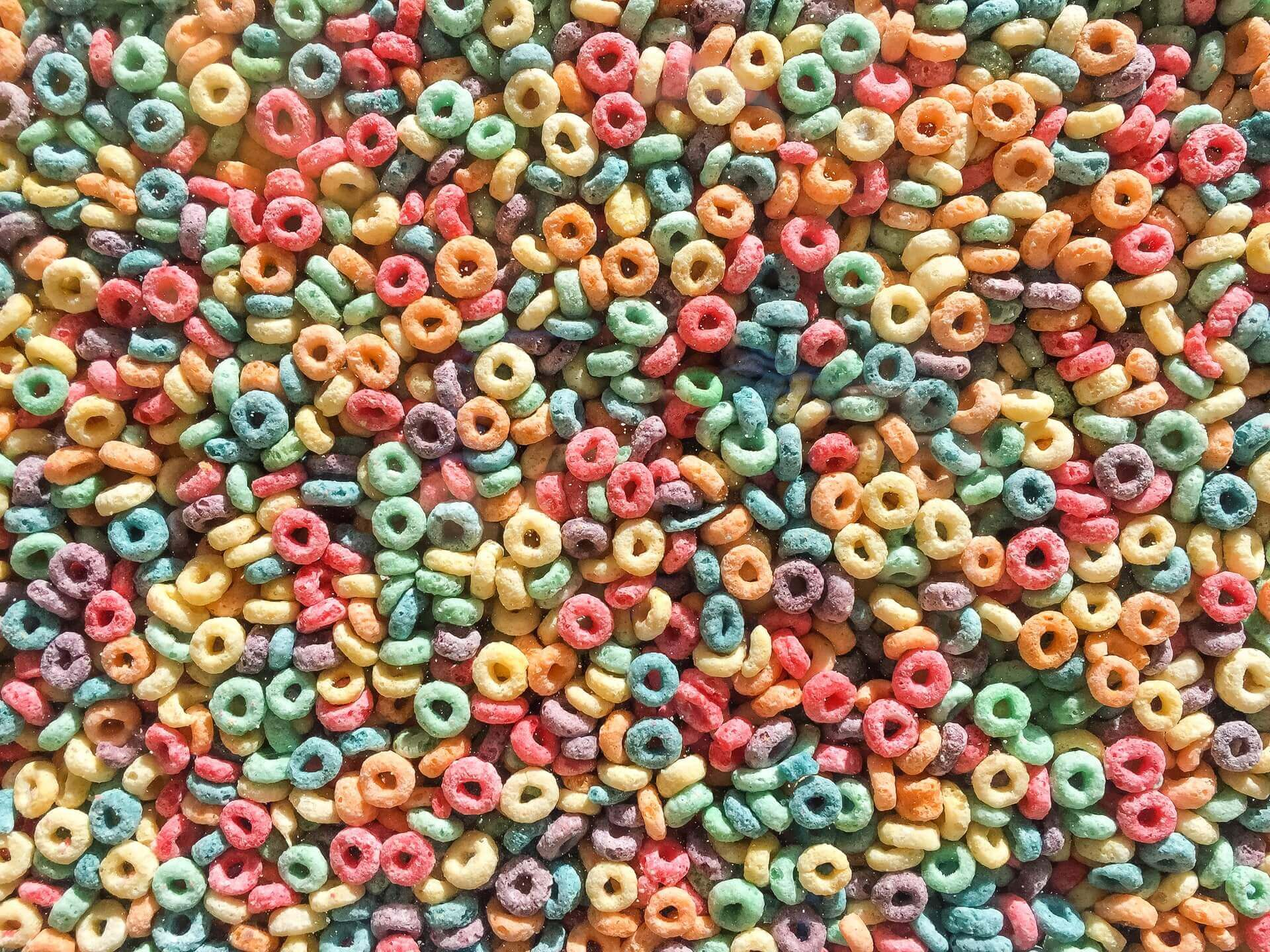 A lot of sugary ring-shaped cereals in a variety of bright colors.