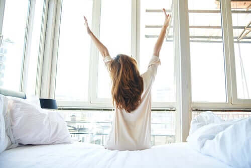 A woman waking up and stretching before a day with less routinization and more creativity.