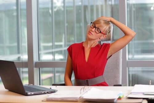 En kvinde foran en skærm strækker ud for at opnå god visuel hygiejne