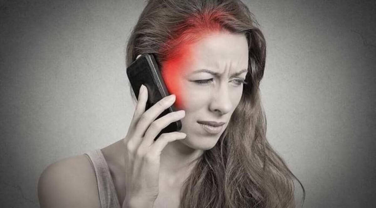 A woman with a headache holding her cell phone.