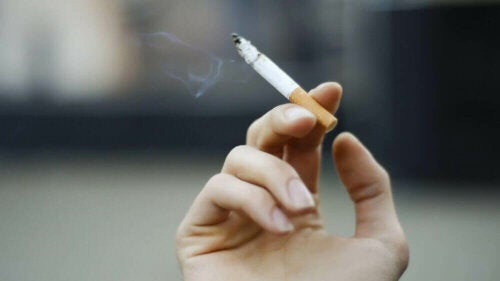 A hand holding a cigarette.