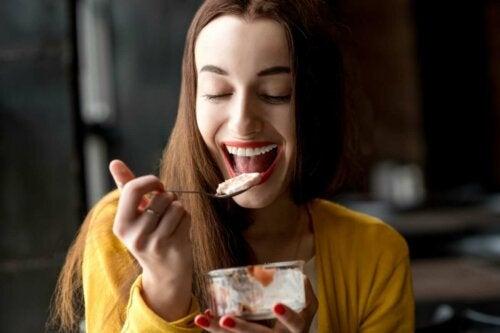 A smiley woman eating yogurt.