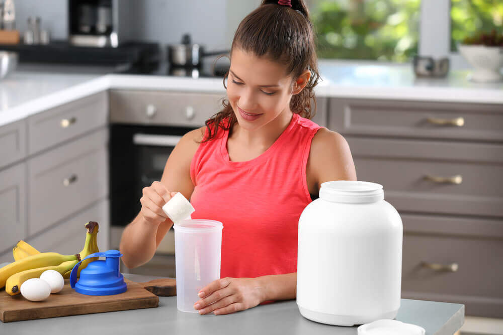 A woman making a protein shake.