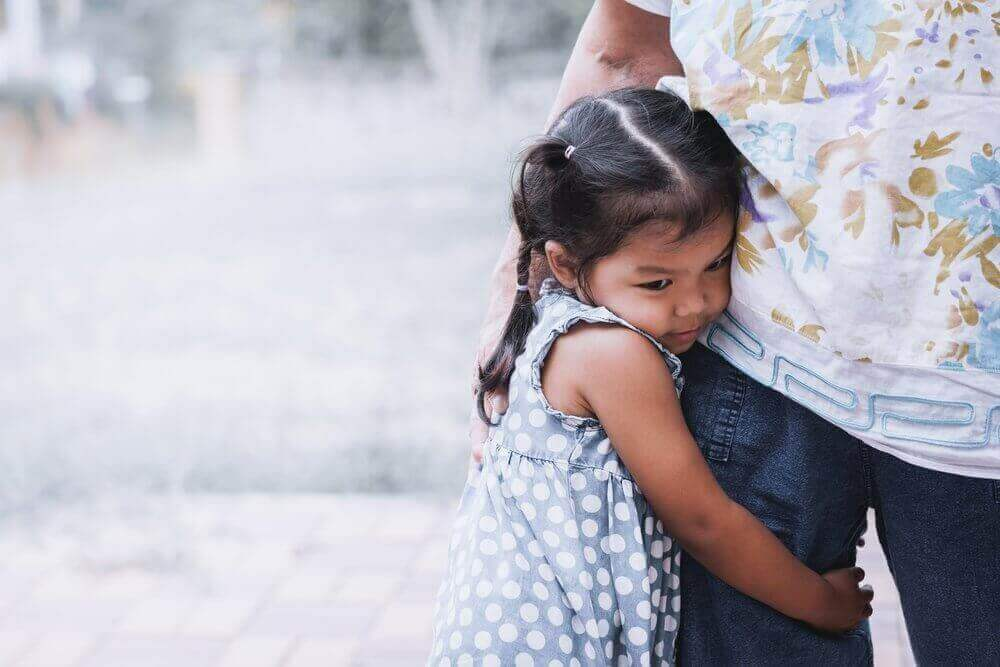A small child clinging to her parent's leg.