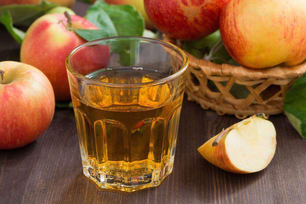 Two glasses of apple juice with whole and cut apples in the background.