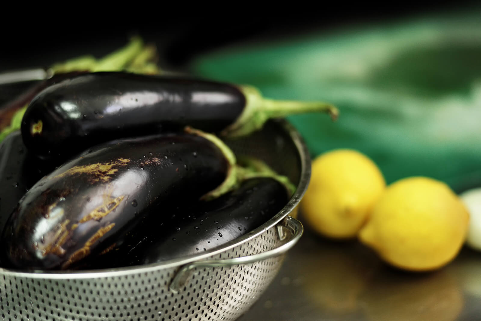 Whole eggplants in a strainer, with whole lemons in the background.