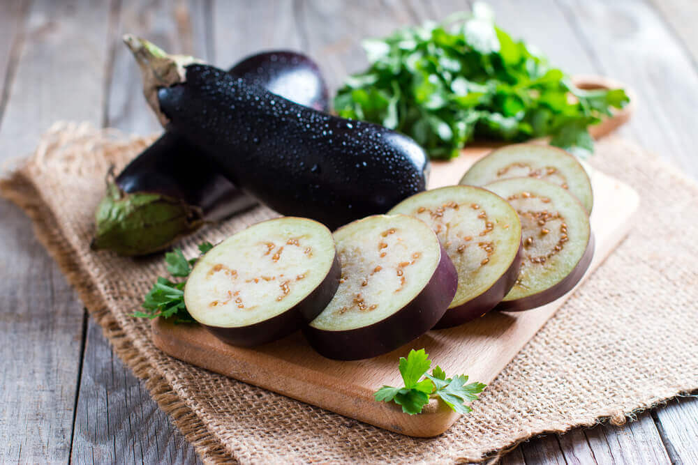 Sliced eggplant on a cutting tray, with whole eggplant and parsley in the background.