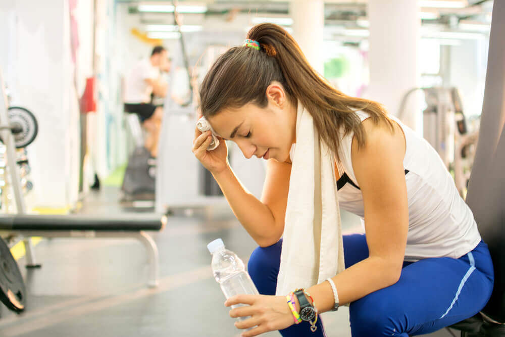A woman at the gym with a bottle of water.