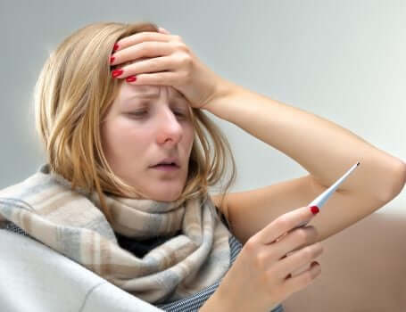 A woman with a fever looking at a digital thermometer.