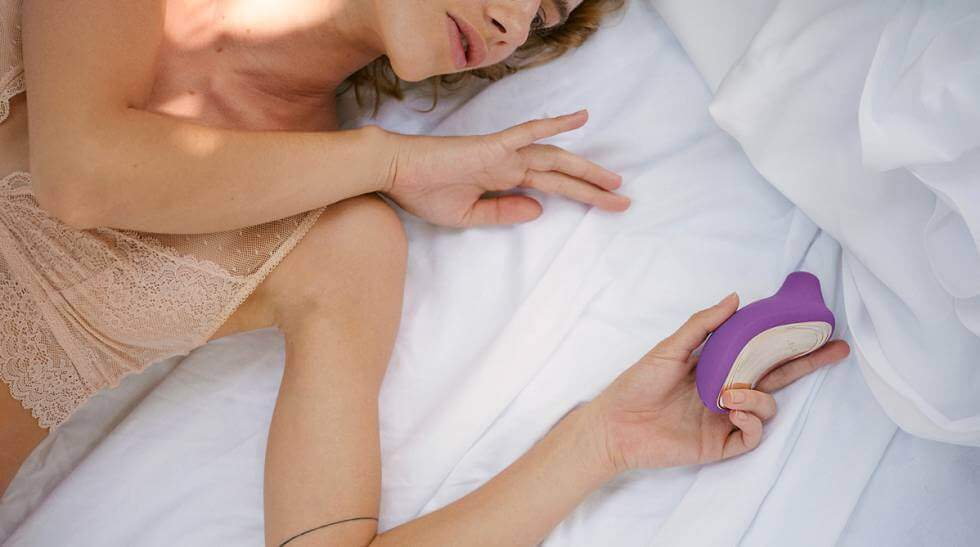 A woman lying in bed holding a clitoris massager, looking to find pleasure.