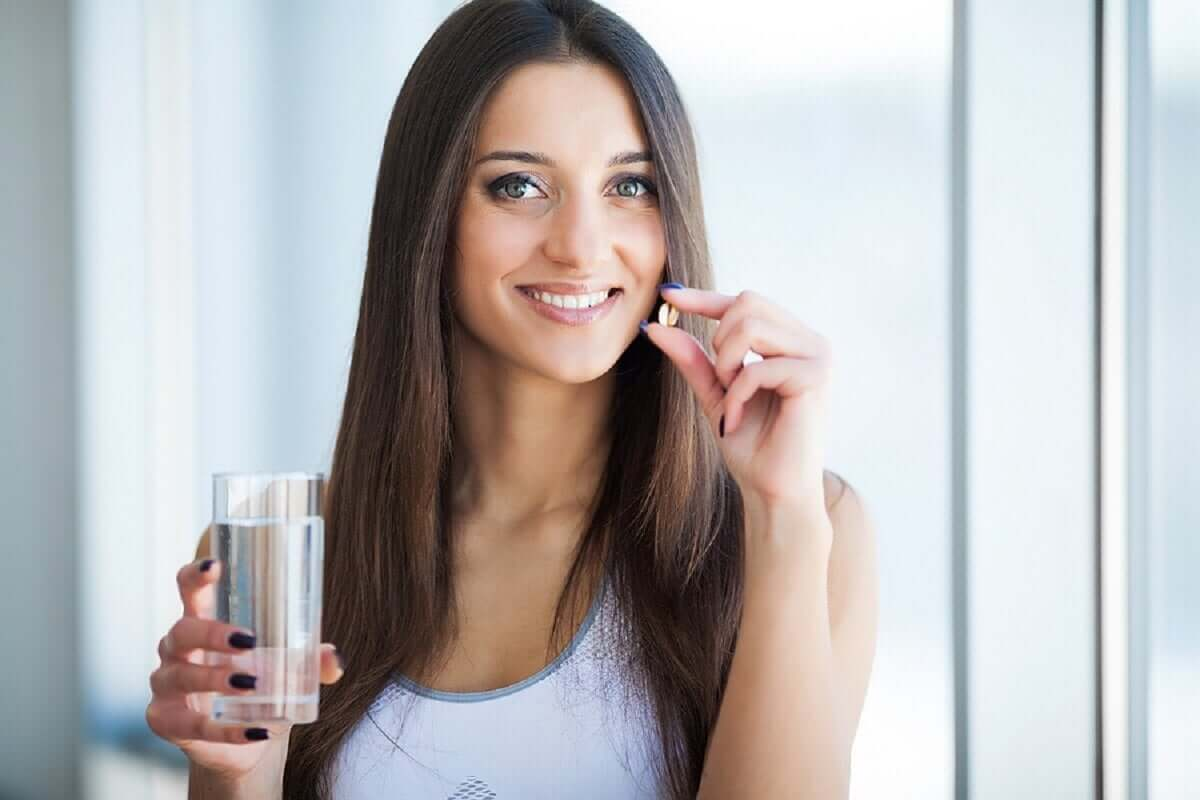 A woman holding two vitamins in one hand, and a glass of water in the other.
