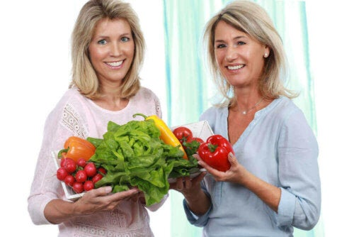 Two women holding fruit and vegetables.