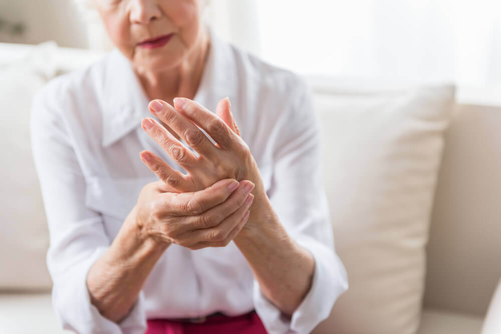 An elderly woman rubbing one hand with the other.