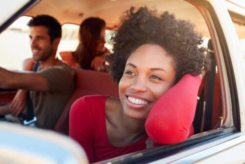 Going on a trip may be a good solution when you don't feel like doing anything. In this photo, a woman feeling happy while on a road trip with friends.