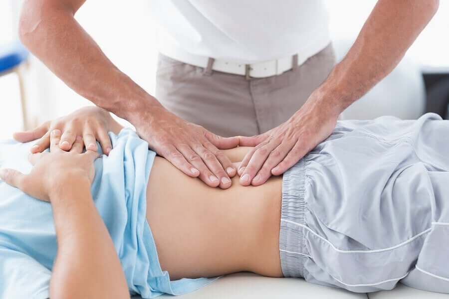 A doctor pressing down on a stomach