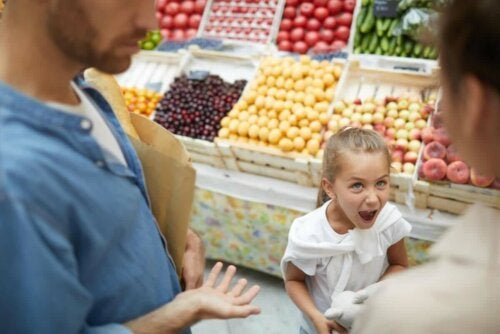 A girl misbehaving at the grocery store.