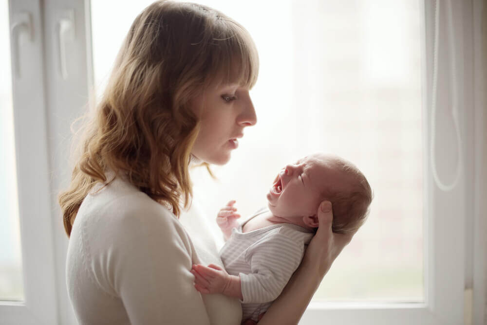 Μια μητέρα με ένα μωρό που κλαίει.