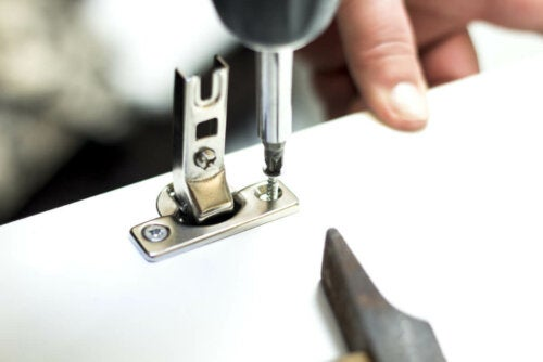 A person removing a hinge.