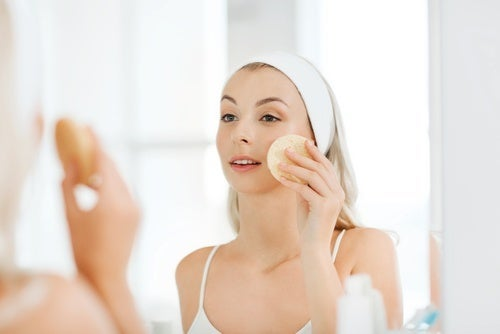 A woman cleaning her face with a sponge.