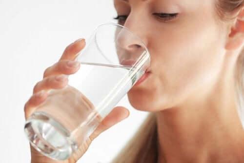 En kvinde, der drikker et glas vand