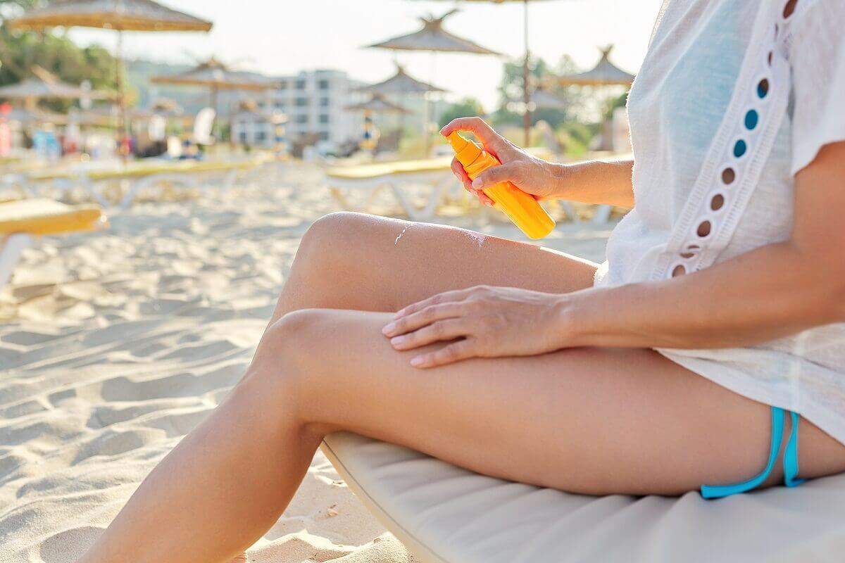 A woman putting on sunscreen.