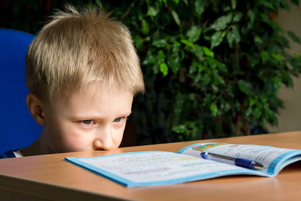 A child looking anxiously at his shool work.
