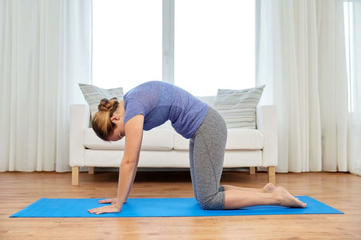 A woman arching her back in order to perform the cat pose.