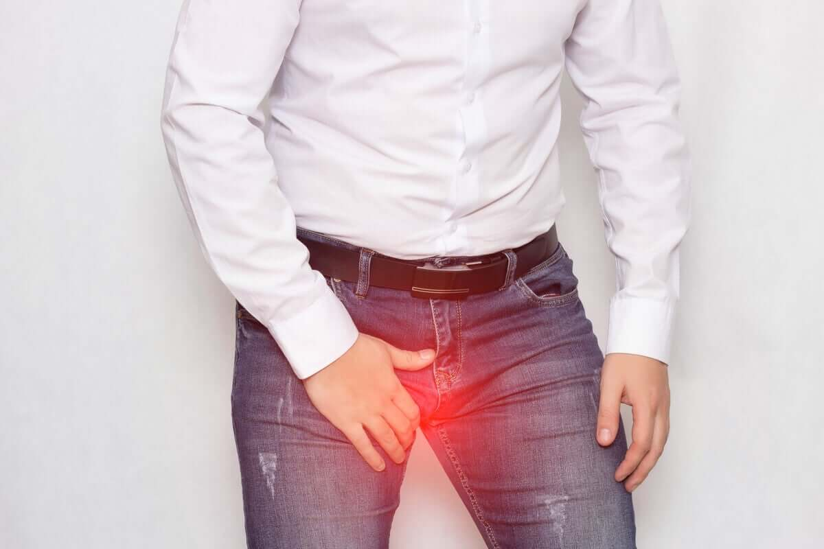 A man hunched over, holding onto his groin.