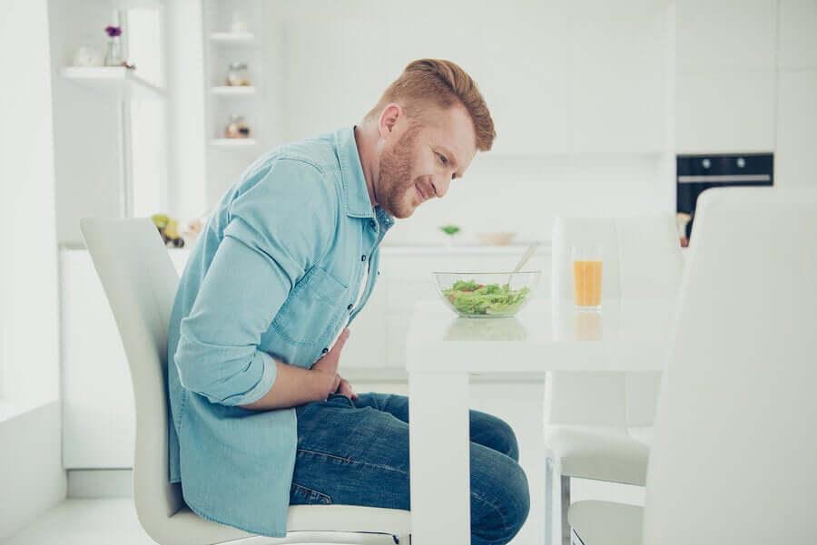 A man eating a salad and having abdominal cramps.