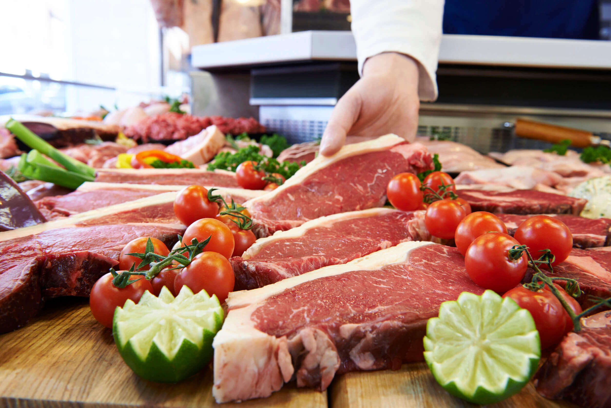 A person picking up a cut of beef.