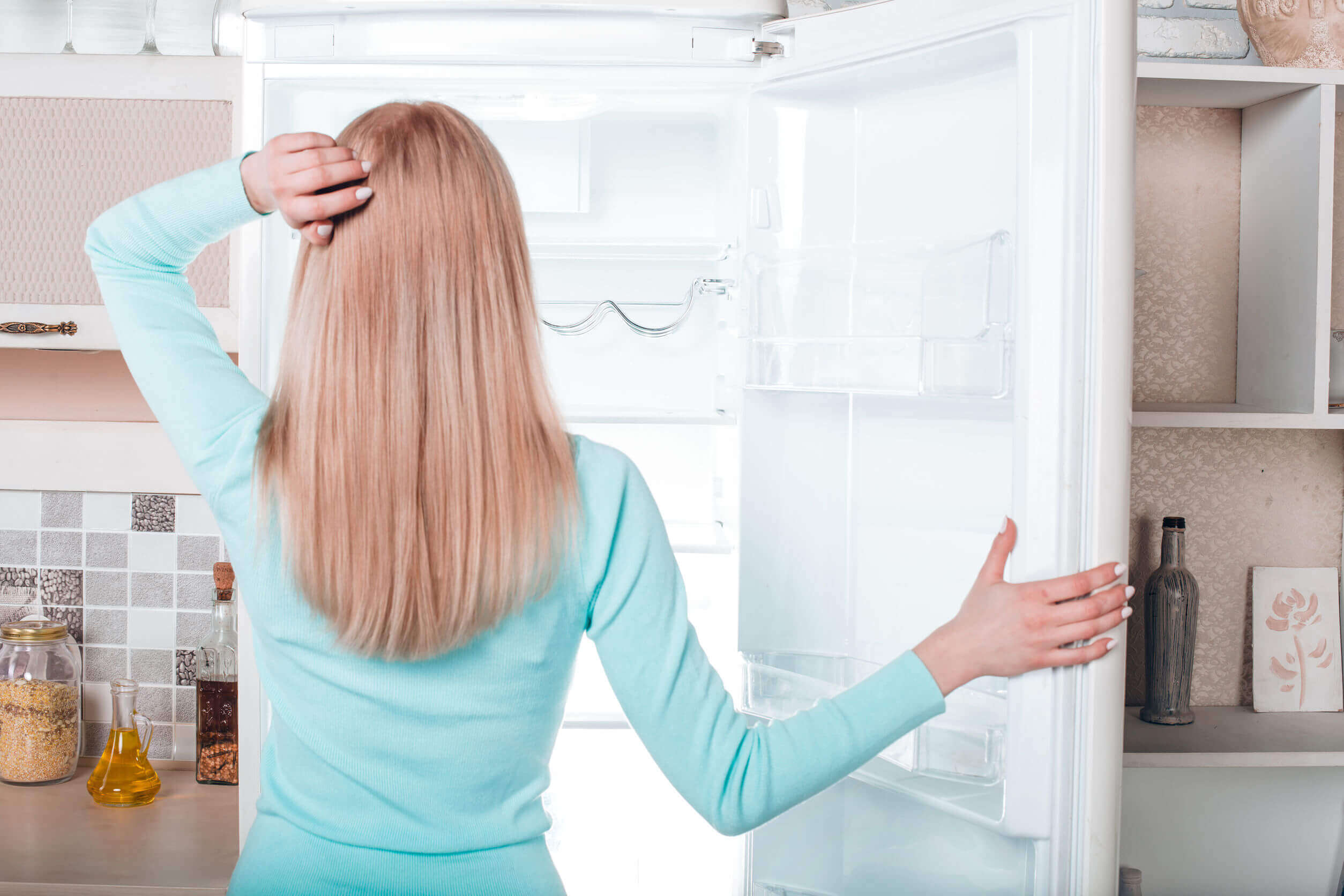 A woman looking at her freezer.