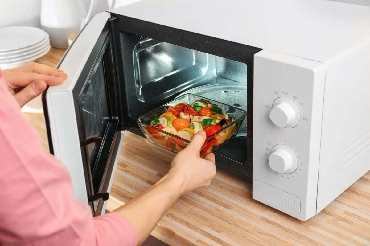 A woman heating food in the microwave using a glass dish.