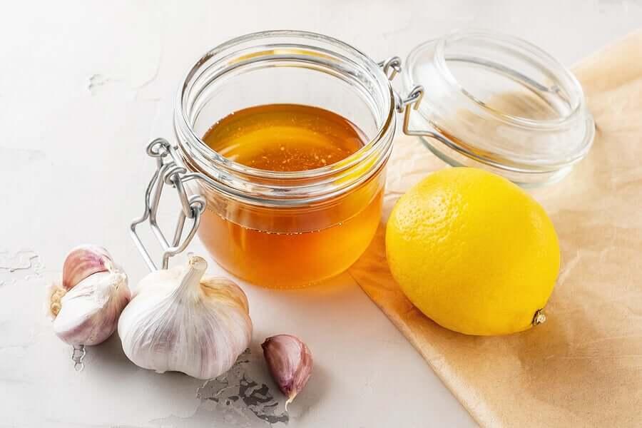 A head of garlic, a jar of honey, and a lemon.