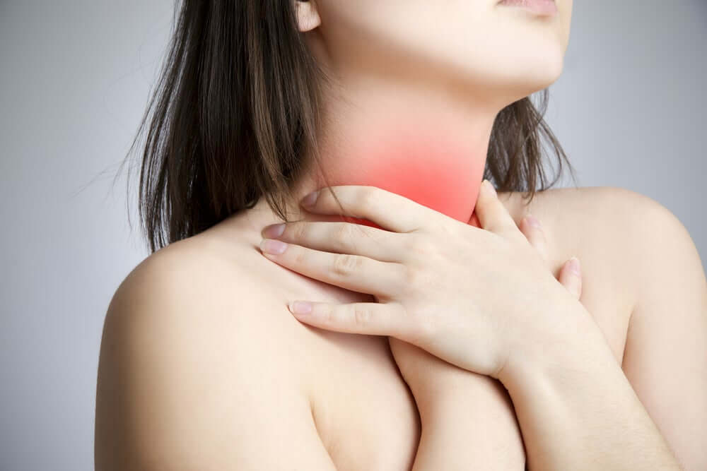 A woman holding onto her sore throat.